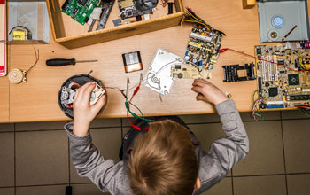 Boy sitting at a desk working on multiple electronic motherboards