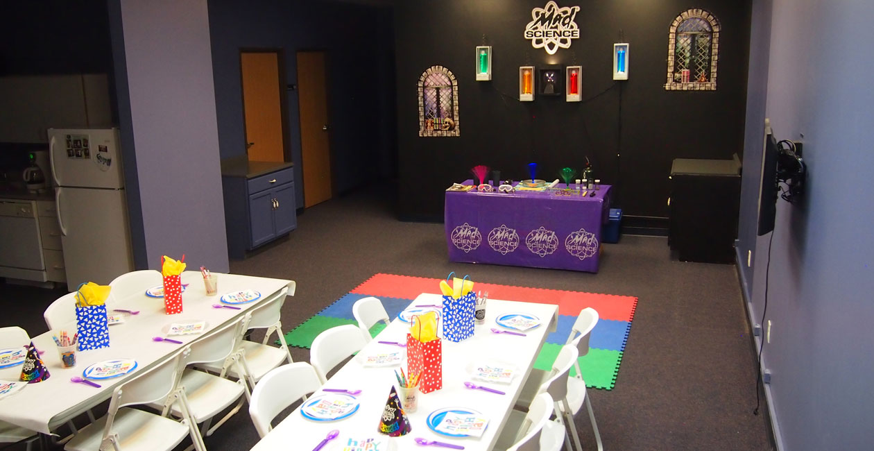 A Mad Science birthday party room set up with 2 tables decorated for a birthday party and a mad science table ready for kid e