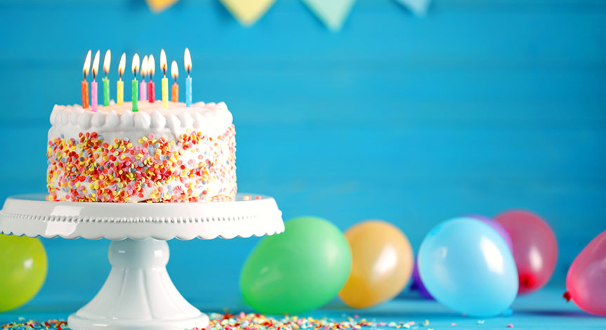 Delicious birthday cake on a white tray with burning candles and colorful balloons on table