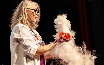 Mad scientist holding a beaker with a red liquid inside and smoke pouring out of it